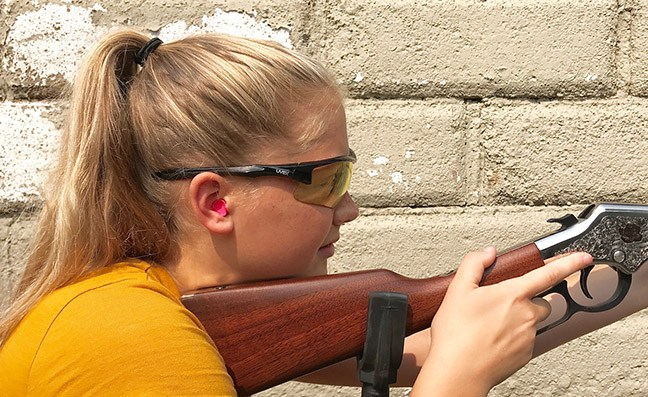 Woman weraing foam ear plugs shooting a rifle for hearing protection