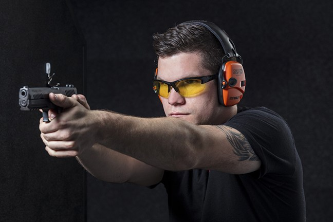 Man with orange earmuuf shooting a pistol with a two-handed grip