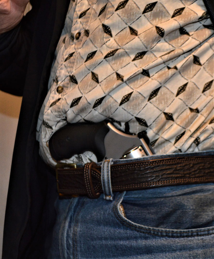 Man with revolver tucked into his waistband to demonstrate holsterless carry
