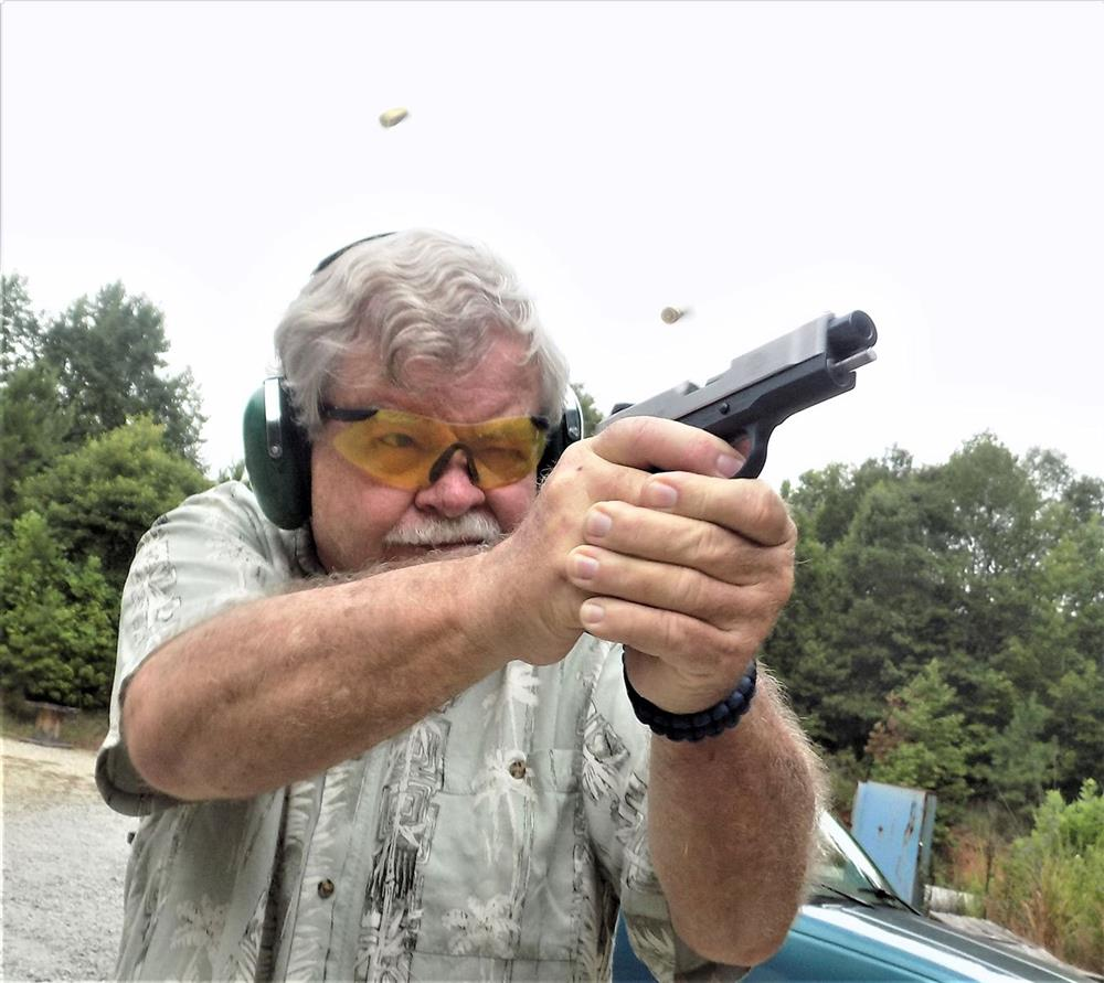 Bob Cambell shooting a pistol with spent cartridge cases in the air