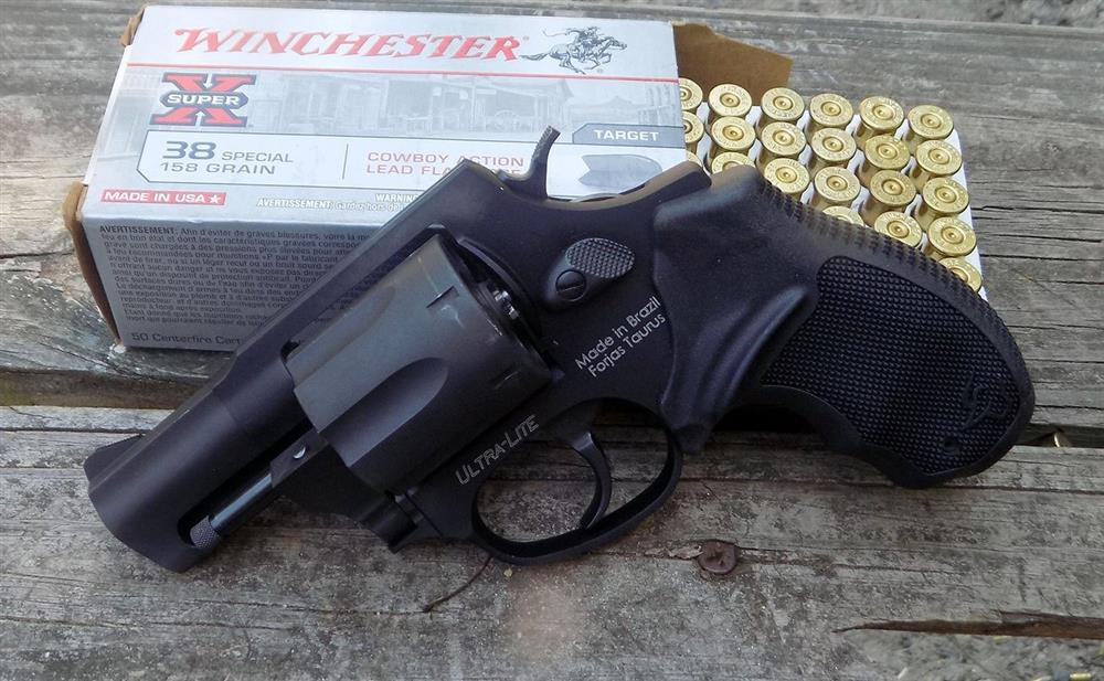 Taurus revolver propped against an open boc of Winchester white box ammunition